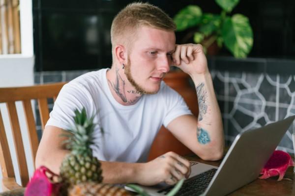 Chico joven buscando recursos para empresas en portatil